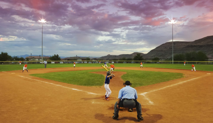 Las Vegas, Nevada - October 18,2014: A Summerlin park on October 18, 2014, in Las Vegas, Nevada. A player bats in a twilight youth baseball game in a Summerlin park in Las Vegas, Nevada.